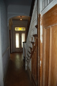 View down front hallway. Lincrusta on the left.  Oak staircase on the right.